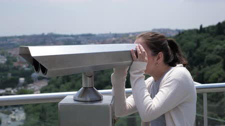 binocular : brunette woman in white sweater looks through binoculars exploring cityscape stretching along bay side view
