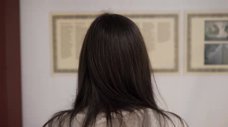 csikk : brunette lady with long hair stands in national art gallery and reads introductory information close backside view Stock mozgókép