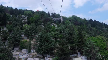 sírkő : view from moving cableway cabin to traditional Muslim cemetery located on hills among green plants under sky with clouds sky