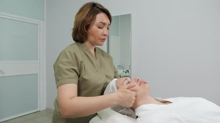 омоложение : beautician does professional face massage to young woman client on beauty table in medical center side view