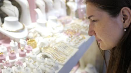 juwelier : joyful girl looks at gorgeous expensive jewelry in window case and makes choice in modern store extreme close view