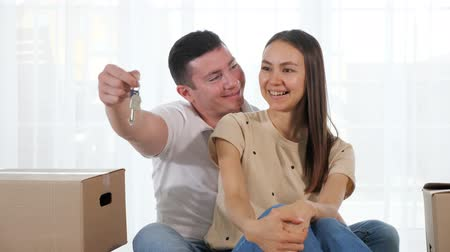 belongings : husband gives keys to beautiful new house to smiling wife sitting on floor against panoramic window with curtain closeup