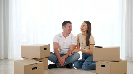 coisas : Young happy couple sitting on the floor of their new apartment among cardboard boxes and planning redecoration