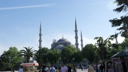 ISTANBULTURKEY - JULY 30 2019: Tourists walk along spacious city square near beautiful ancient mosque with high minarets in Istanbul slow motion on July 30 in Istanbul