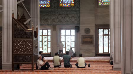 ISTANBULTURKEY - JULY 30 2019: Muslim men pray in beautiful mosque with large stained glass windows and columns in Istanbul backside view slow motion on July 30 in Istanbul