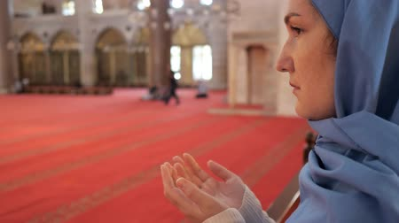 головной платок : thoughtful woman in blue headscarf prays holding hand palms up standing in ancient mosque extreme close view Стоковые видеозаписи