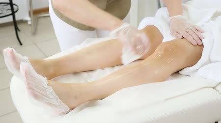 woman hands in rubber gloves apply lidocaine gel on slender girl leg lying on soft sheets in medical center