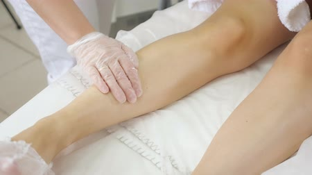 beautician hands apply after laser epilation treatment on hairless leg in professional medical center close view Stock Footage