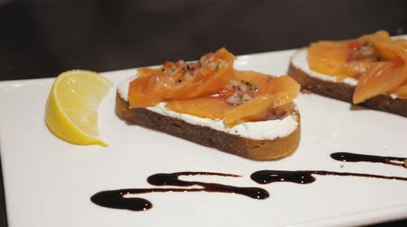 バゲット : Bruschetta with salmon on a white plate, close up. 動画素材