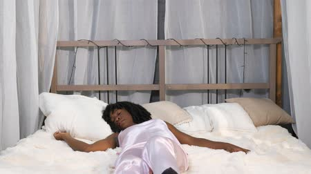 minder : attractive African American girl with curly hair lies on large bed and wakes up suddenly in stylish bedroom slow motion Stok Video