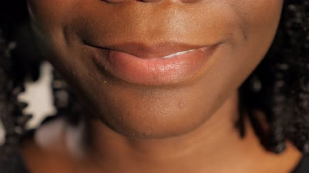 歯を見せる : pretty young African woman with black curly hair smiles cheerfully showing white teeth slow motion extreme close view