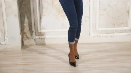 elevação : slim black lady legs in jeans and dark high heeled shoes dance on white floor slow motion close low angle shot