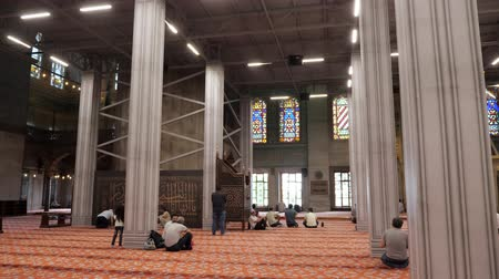 bum : ISTANBULTURKEY - JULY 30 2019: Muslim men pray in beautiful mosque with large stained glass windows and columns in Istanbul backside view slow motion on July 30 in Istanbul