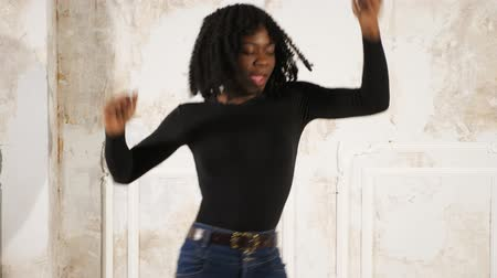 хайтек : active young slim black woman in jeans and pullover dances in high heeled shoes against beige wall slow motion