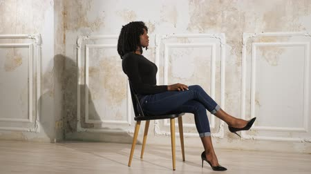high heel shoe : exciting black lady in dark clothes sits cross-legged on wooden chair in room with beige floor walls slow motion side view