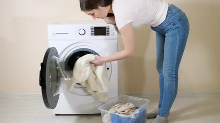 mindennapi : young housewife loads dirty clothes into modern washing machine from plastic box near beige wall