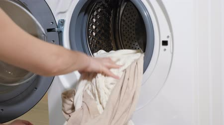mindennapi : long haired girl in t-shirt takes clean laundry of modern washing machine close-up Stock mozgókép