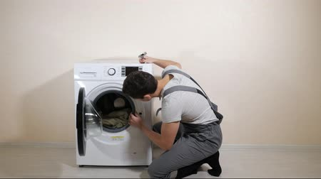toolbox : young serviceman in grey uniform repairs broken washing machine with wrench on wooden floor near beige wall