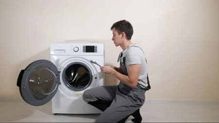 гарантия : young serviceman in grey uniform repairs broken washing machine with wrench on wooden floor near beige wall