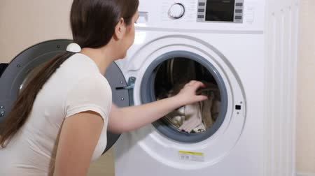 mindennapi : long haired woman in t-shirt takes clean laundry of modern washing machine near beige wall slow motion closeup