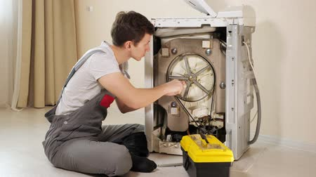 tesisatçı : professional master in grey jumpsuit pants opens back panel of broken washing machine top loader by beige wall