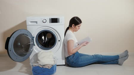 mindennapi : upset woman with dirty laundry in box and manual in hands sits on floor by modern washing machine in room Stock mozgókép
