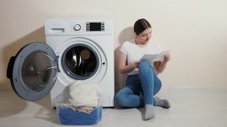 mindennapi : pretty girl in jeans reads instruction for new washing machine sitting on wooden floor near beige wall Stock mozgókép