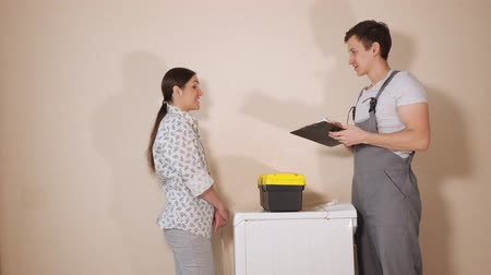 toolbox : positive serviceman with clipboard and toolbox visits brunette housewife to check broken washing machine in room Stock Footage