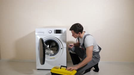 encanador : skilled serviceman in grey uniform with toolbox comes to check modern washing machine in light room Vídeos