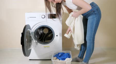mindennapi : young brunette girl loads dirty clothes into modern washing machine from plastic box near beige wall Stock mozgókép