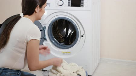 mindennapi : pretty housewife loads dirty clothes into new washing machine sitting on wooden floor in light room