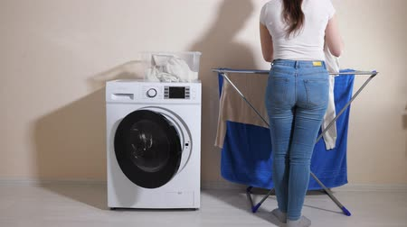 mindennapi : brunette lady takes laundry of washing machine and hangs out clothes on rack near beige wall at home