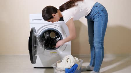 mindennapi : young brunette woman loads dirty clothes into modern washing machine from plastic box near beige wall