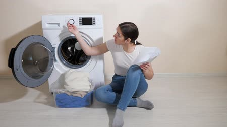 mindennapi : young housewife learns settings of new washing machine with instruction sitting on floor in light room Stock mozgókép