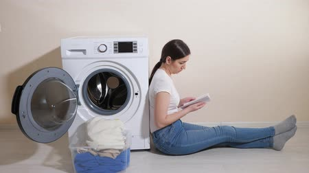 mindennapi : upset young woman with dirty laundry in box and manual in hands sits on floor by modern washing machine in room