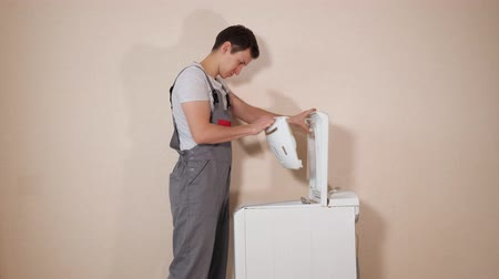 гарантия : young worker in grey uniform opens loader cover on top of broken washing machine to mend appliance near beige wall