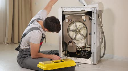 moersleutel : professional master in grey jumpsuit pants opens back panel of broken washing machine top loader close-up