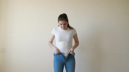 tutturma : A woman in a white t-shirt bounces into her jeans and struggles to button them.
