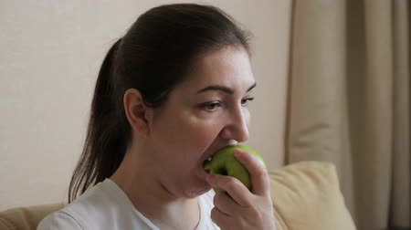 круглолицый : plump woman is eating an apple while sitting on the sofa, close-up