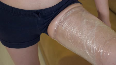 material body : An overweight woman wraps her thighs in plastic wrap. Method of weight loss, closeup Stock Footage
