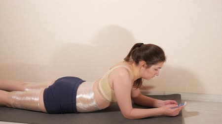 sal : woman is lying on a gym mat with a phone. Thighs and belly wrapped in plastic wrap, side view