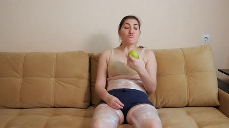 material body : Woman eating an apple sitting on the couch. Thighs and belly wrapped in plastic wrap. Stock Footage