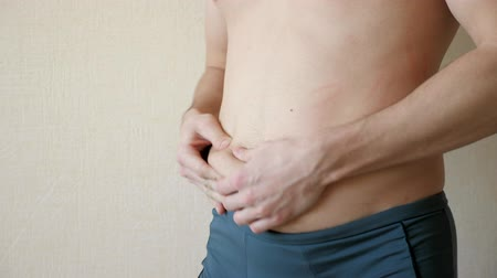 kalhotky : young man palpates his stomach and sides, closeup