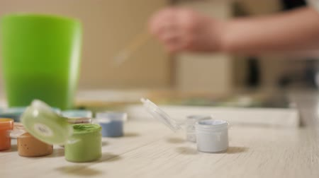 グワッシュ水彩画 : Jars of paint in focus. artist girl draws on blurred background. 動画素材