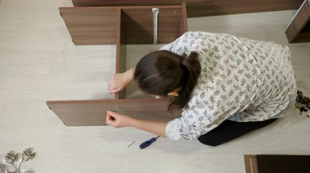 組み立てる : woman with dark hair sits on floor and assembles new prefabricated cabinet rotating tool to connect shelf parts top view 動画素材