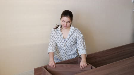 lakásfelújítás : brunette girl in home clothes sits on kitchen floor and tries to assemble prefabricated wooden cupboard parts closeup Stock mozgókép