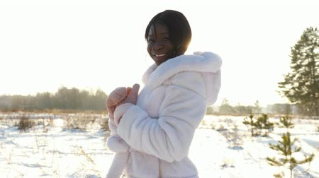 smiling nice dark-skinned girl in white fur coat and warm mittens poses against snowy field at back sunlight closeup