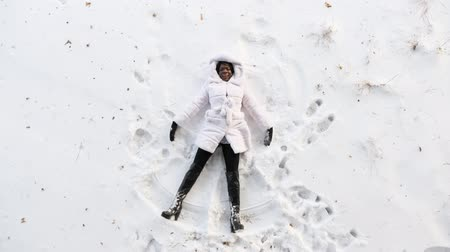 black girl in fur coat and high top boots lies on white glade and draws snow angles picture with arms and legs top view