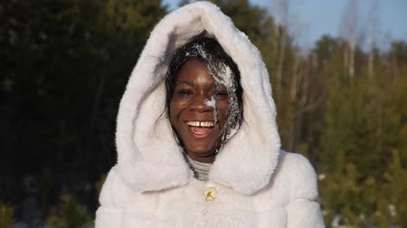 pretty happy lady with snow on face smiles having fun at photoshoot in forest closeup slow motion Stock Footage