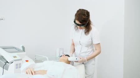 skilled therapist in white coat and black sunglasses makes laser hair removal on beauty salon patient face zoom in